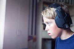 Teenager, der Computerspiele auf PC spielt Stockfotografie