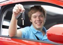 Teenager, der in den Auto-Holding-Auto-Tasten sitzt Lizenzfreies Stockbild