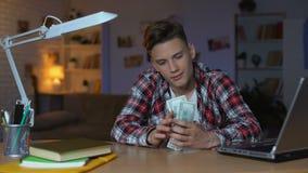 Teenager, der die Dollarscheine denken an die Neuanschaffung, träumend zählt stock video