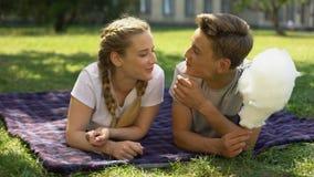 Teenager, der die Zuckerwatte und Küssen, liegend auf Plaid im Park, Verhältnis isst stock footage