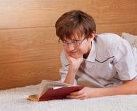 Teenager, der ein Buch liest Stockbild