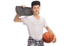 Teenager, der ein Skateboard und einen Basketball hält Lizenzfreies Stockbild