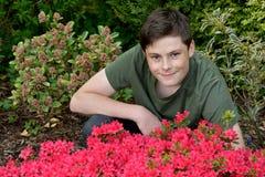 Teenager, der für Fotos im Garten aufwirft Stockbild