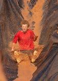 Teenager, der hinunter Wasserrutsche in einem Schlammlauf schiebt stockfotografie