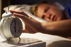 Teenager, der im Bett aufwacht und Wecker abstellt Stockbild