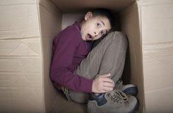 Teenager, der im Sammelpack sich versteckt Stockbild