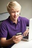Teenager, der im Schlafzimmer auf Handy liegt Lizenzfreie Stockfotos