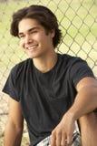 Teenager, der im Spielplatz sitzt stockfoto