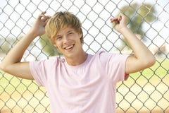 Teenager, der im Spielplatz sitzt Lizenzfreie Stockfotos