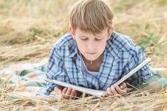Teenager, der mit Buch liegt Stockfoto