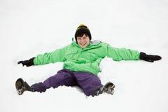 Teenager, der Schnee-Engel auf Steigung bildet Stockbild