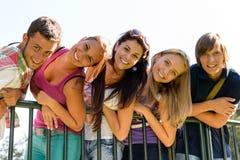Teenager, der Spaß in lehnendem Zaun des Parks hat Lizenzfreie Stockfotos