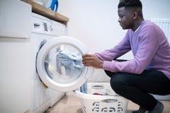 Teenager, der zu Hause bei den inländischen Aufgaben leeren Waschmaschine hilft lizenzfreie stockfotos
