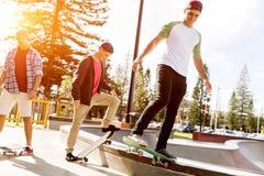 Teenager, die draußen Skateboard fahren Stockfoto