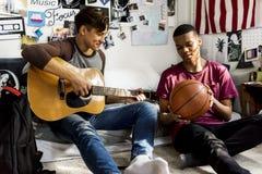 Teenager, die heraus in einem Schlafzimmermusik- und Sporthobbykonzept hängen lizenzfreie stockfotografie