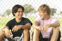 Teenager, die im Spielplatz sitzen Lizenzfreies Stockbild