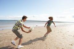 Teenager, die Rugby auf Strand spielen Stockfotos