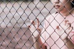 Teenager dietro la gabbia o la donna imprigionata fotografia stock libera da diritti