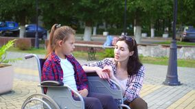 Teenager disabled in a wheelchair talking to a girl. A disabled teenager in a wheelchair communicates on the street with a girl in a shirt stock footage