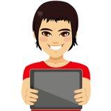 Teenager Displaying Tablet. Young teenager boy displaying tablet on horizontal position Royalty Free Stock Image