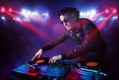 Teenager dj mixing records in front of a crowd on stage Stock Photography