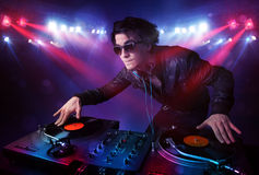 Teenager dj mixing records in front of a crowd on stage Royalty Free Stock Images