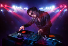 Teenager dj mixing records in front of a crowd on stage Stock Images