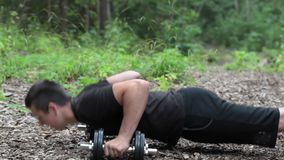 Teenager do push ups at outdoor stock video footage
