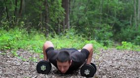 Teenager do push ups in the park stock video footage