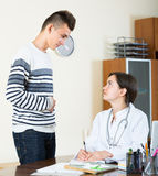 Teenager and doctor at desk in clinic Stock Images
