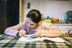 Teenager does her homework in the home kitchen on the table help. Ing herself with the smartphone Royalty Free Stock Image
