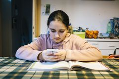 Teenager does her homework in the home kitchen on the table help. Ing herself with the smartphone Stock Photography