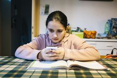 Teenager does her homework in the home kitchen on the table help. Ing herself with the smartphone Stock Image
