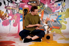 Teenager dog urban graffiti. Male teenager with dog enjoying music from speakers in front of graffiti wall, urban setting.  Studio shoot Stock Images
