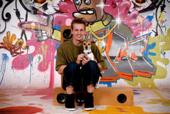 Teenager dog urban graffiti. Male teenager with dog enjoying music from speakers in front of graffiti wall, urban setting.  Studio shoot Stock Image