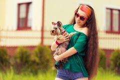 Teenager with dog yorkshire terrier on hands. Outdoors closeup portrait Royalty Free Stock Images