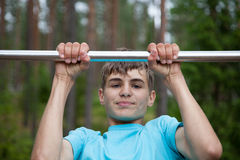 Teenager doing exercise on a horizontal bar Royalty Free Stock Photos