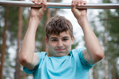 Teenager doing exercise on a horizontal bar. The teenager doing exercise on a horizontal bar Royalty Free Stock Photos
