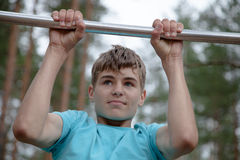 Teenager doing exercise on a horizontal bar Royalty Free Stock Photography