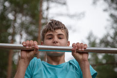 Teenager doing exercise on a horizontal bar Royalty Free Stock Images