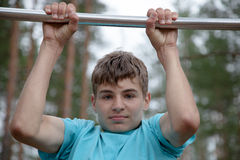 Teenager doing exercise on a horizontal bar Stock Photos