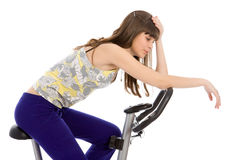 Teenager doing fitness on a stationary bike Stock Image