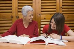 Teenager doing homework. Teenager sitting at the table doing the homework with the help of her grandmother Stock Photo