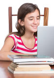 Teenager doing homework or browsing the web on her laptop Royalty Free Stock Photography