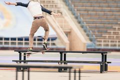 Teenager doing a trick by skateboard on a rail in skate park Stock Images