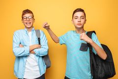 The teenager threatens, naughty brother, fist, on a yellow background royalty free stock image