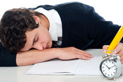 Teenager dozing off while writing his test. Fast asleep royalty free stock photos