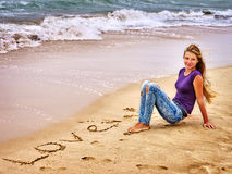 Teenager draw love on sand near waves. Summer girl sea.  Teenager draw love on sand near waves Royalty Free Stock Image