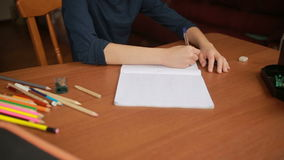 A teenager draws a simple pencil in a notebook. Close-up stock video