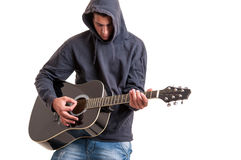 Teenager dressed in a hoodie, writing a song about life. Pensive Teenager dressed in a hoodie, writing a song about life at acoustic guitar Stock Photo